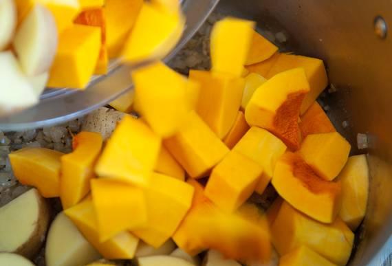 4. К обжаренному луку с чесноком можно отправить картофель и тыкву. Аккуратно перемешать и оставить на сковороде на 3-5 минут.