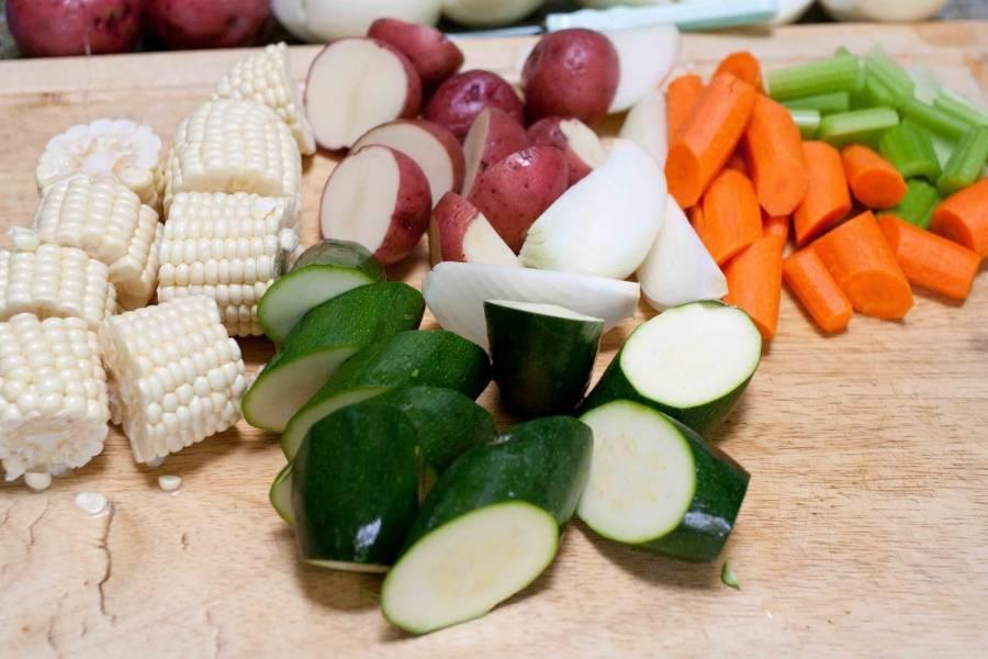 Добавьте лавровый лист и специи в бульон. Тем временем порежьте овощи на средние кусочки.