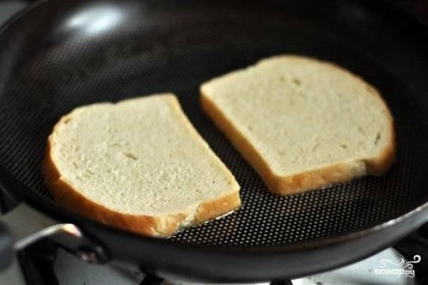 На разогретую сковороду налейте немного оливкового масла. Выложите белый хлеб в сковороду и обжарьте до золотистой корочки. Хлеб нужно обжарить с обеих сторон.
