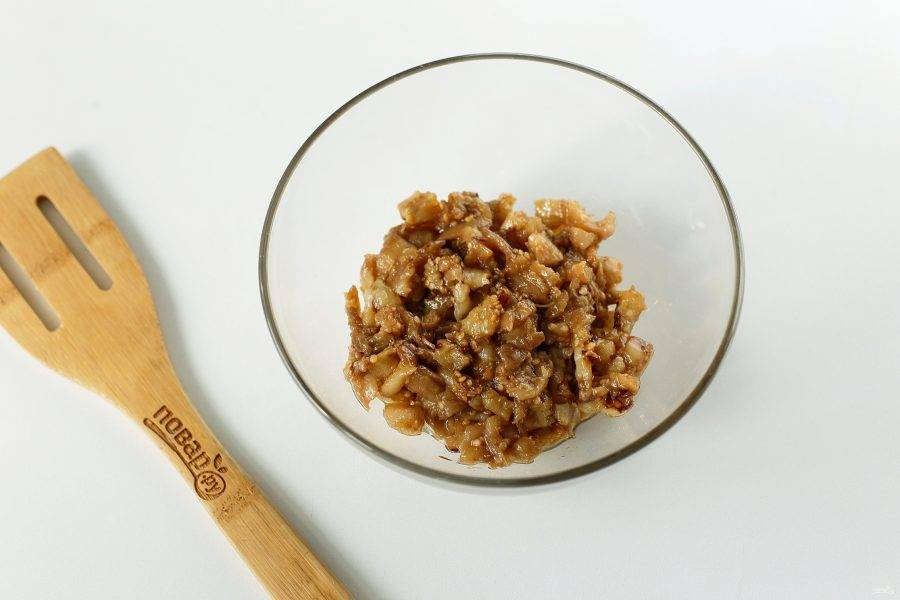 Вырежьте из баклажанов мякоть, сформировав лодочки. Измельчите мякоть ножом и переложите в глубокую миску.
