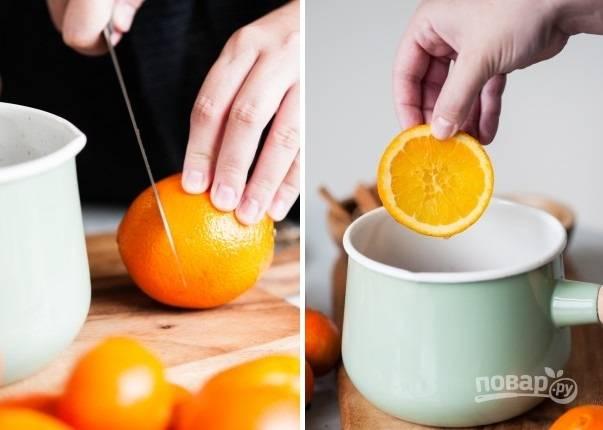 5. Оставшиеся апельсины нарежьте тонкими ломтиками и добавьте в напиток. Уберите огонь до минимума и томите минуты 3, чтобы глинтвейн как следует пропитался ароматами. Перед подачей на стол процедите его, чтобы убрать специи.