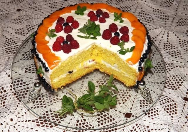 Готовый торт бисквитный с фруктами лучше отправить на ночь в холодильник для пропитки, тогда он станет гораздо вкуснее. В разрезе видна прослойка из фруктов. Перед подачей можете украсить листиками мяты. Приятного аппетита!