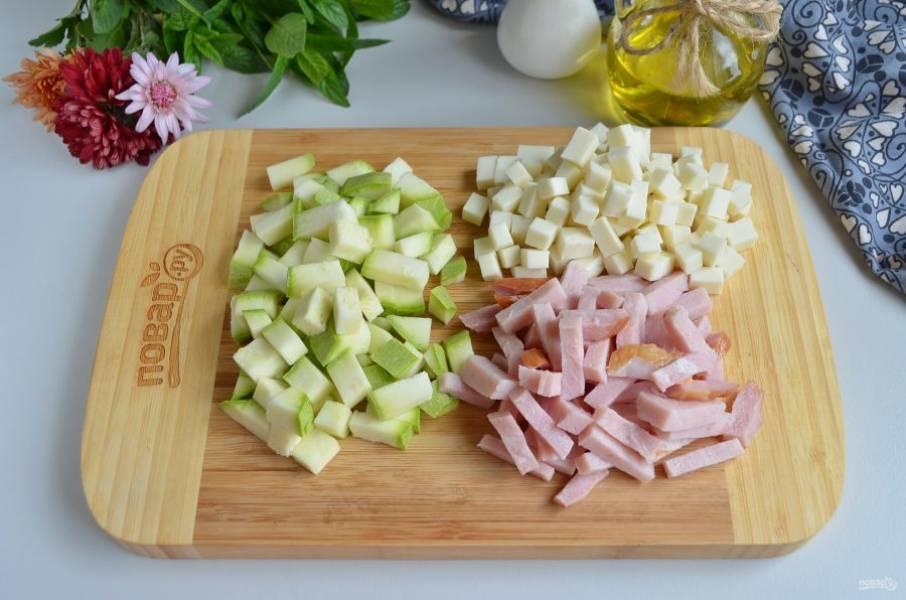 Порежьте небольшими брусочками или кубиками цукини, сыр, ветчину.