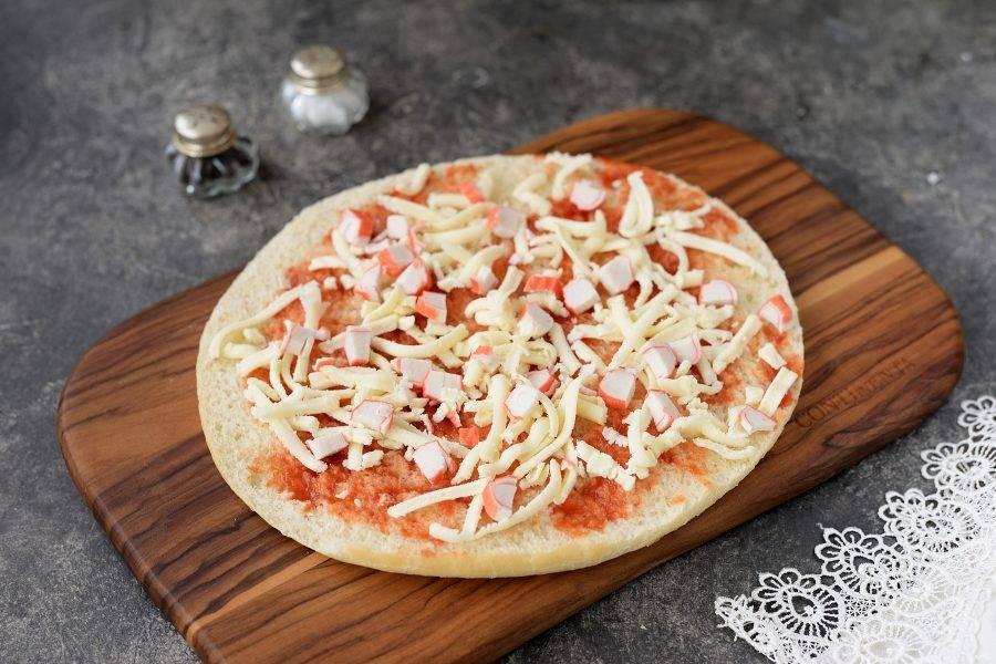 Каждый корж для пиццы разрежьте длинным ножом вдоль на две части одинаковой толщины. Одну половину слегка смажьте любимым томатным соусом, щедро посыпьте натертой моцареллой и нарезанными крабовыми палочками.