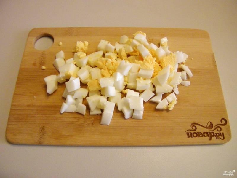 Теперь нарежьте кубиками очищенные яйца.