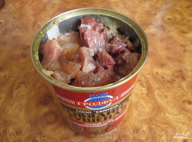 Возьмите тушенку. Если куски мяса слишком крупные, порежьте мельче.