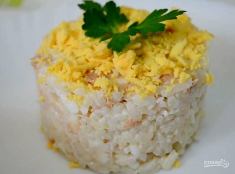 6. Украсьте зеленью и подавайте к столу. При желании такой салат с рисом и рыбными консервами можно разнообразить морковью или свежим огурцом, а также твердым или плавленым сыром.