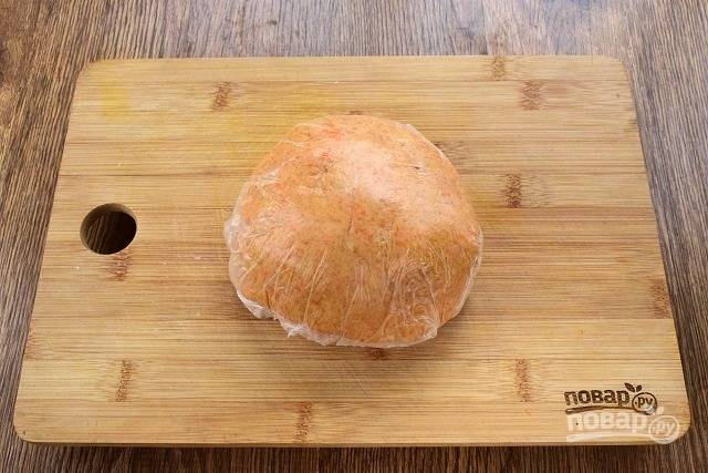 Соедините в глубокой миске ингредиенты для теста: муку, разрыхлитель, сахар (2 ст. л.), холодное сливочное масло, запеченную тыкву и замесите мягкое тесто. В зависимости от сочности тыквы регулируйте количество муки, ее может понадобиться чуть больше или меньше. Тесто должно собраться в шар и не прилипать к рукам. Заверните тесто в пищевую пленку и оставьте в холодильнике на 40-50 минут.