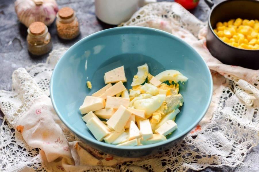 Куриное яйцо отварите заранее и остудите, нарежьте небольшими кусочками и переложите в салатник. Плавленый сыр возьмите с зеленью или со вкусом бекона, нарежьте сыр кусочками и добавьте к яйцу.