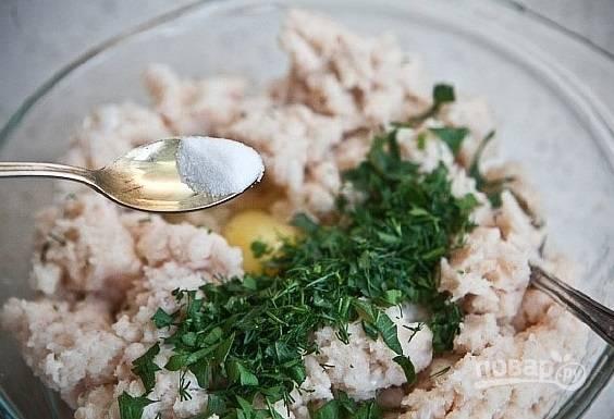 К фаршу добавьте измельчённую и промытую петрушку, соль, яйцо и перец. Всё перемешайте.