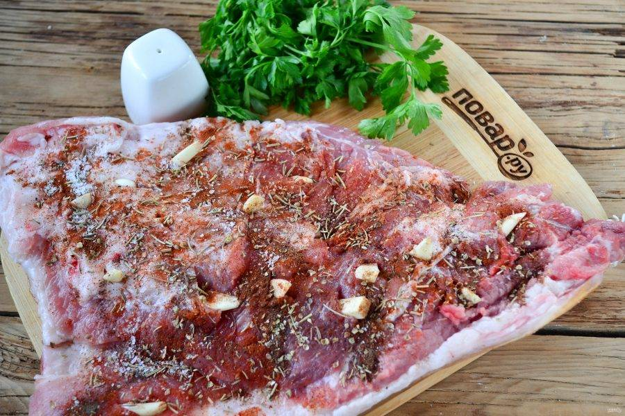 Мясо разложите на рабочей поверхности. Сделайте небольшие разрезы, вложите кусочки чеснока. Смесью специй и соли натрите мясо, хорошо помассируйте его, чтобы специи максимально хорошо пропитали мясо.