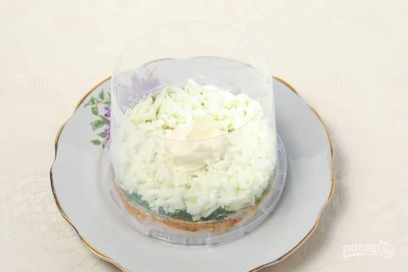 В кастрюльке отварите яйца в крутую (в течение десяти минут). Остудите их и очистите от скорлупы. Затем отделите белки от желтков и натрите их на терке. Выложите слой белков в кольцо и смажьте майонезом.