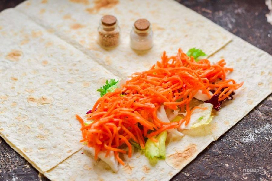 Лаваш расстелите на рабочей поверхности, выложите салатные листья, поверх выложите морковь по-корейски.