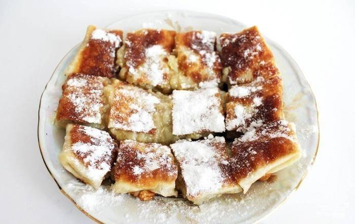 Готовый десерт нарежьте квадратиками. Украсьте его сахарной пудрой и подавайте к столу. Приятной дегустации!
