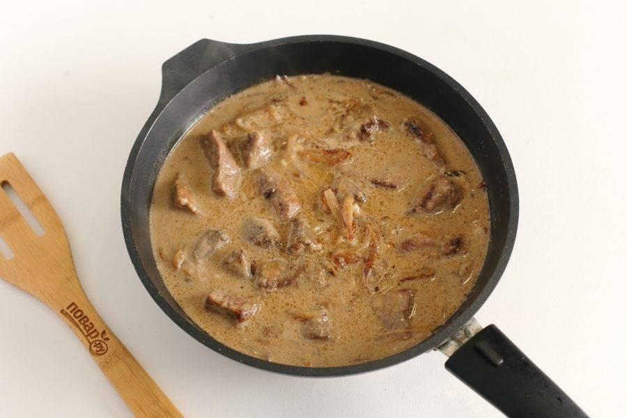Затем добавьте необходимое количество сметаны, соль по вкусу, специи и влейте тонкой струйкой нужное количество воды. Тушите печень в подливе еще около 2-3 минут.