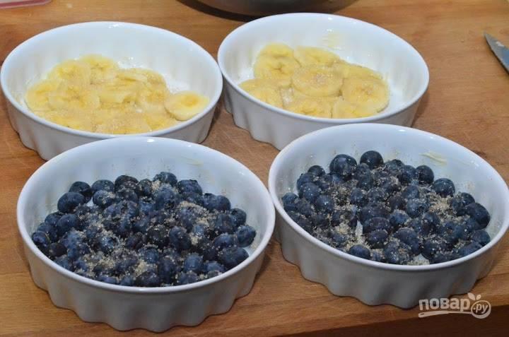 Равномерно уложите на дно формочек ягоды или фрукты (например, голубику и бананы). Слегка посыпьте сахаром.
