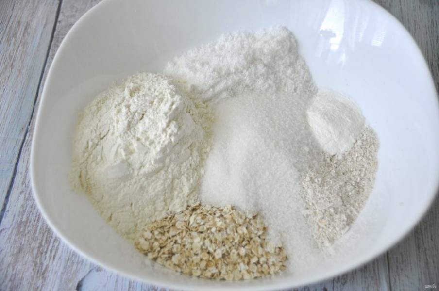 В миску для замешивания теста выложите все сухие ингредиенты: овсяные хлопья, муку, соль, сахар, разрыхлитель (или соду), кокосовую стружку.