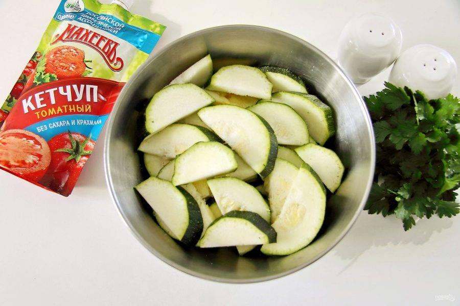 Кабачки нарежьте кружочками, толщиной 5-7 мм (если они молодые, чистить не нужно). Затем каждый кружок разрежьте еще пополам. Перемешайте в миске с солью. По желанию можно использовать любые специи по вкусу.