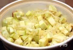 В кастрюлю с толстым дном налить масло, добавить капусту и кабачки, поставить на средний огонь.