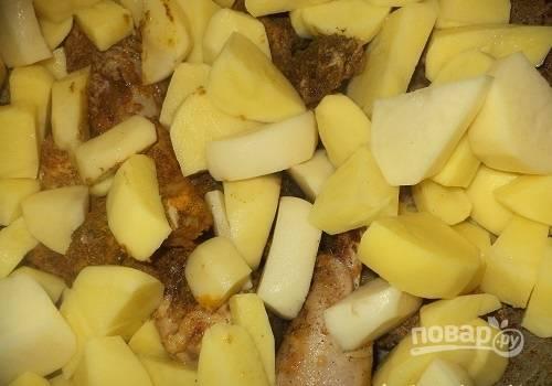 Когда курица будет наполовину готова, добавляем к ней нарезанный картофель и хорошенько все перемешиваем. Доливаем воду и тушим на протяжении 15-20 минут под крышкой.
