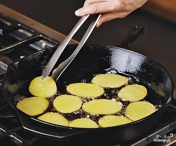 4. Картофель вымойте, очистите (молодой можно оставить в кожуре) и обсушите. Нарежьте тонкими ломтиками. Разогрейте на сковороде оливковое масло и обжарьте на сильном огне картофель до румяности с двух сторон. Также можно в рецепт приготовления мусаки использовать картофельное пюре.