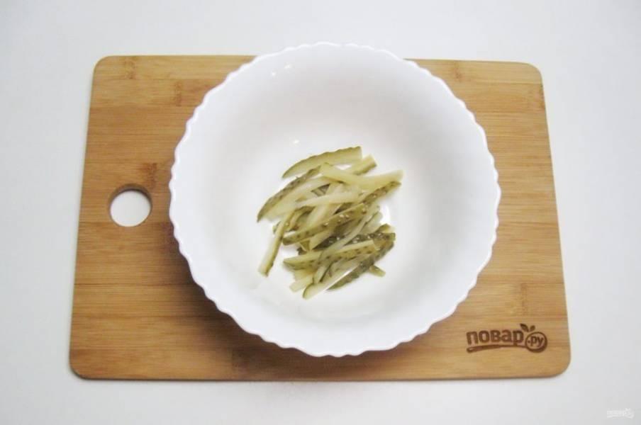 Огурец нарежьте соломкой и выложите в салатник.