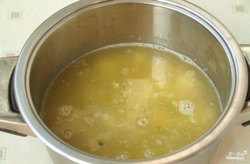 Разогрейте в кастрюле масло. Пропассируйте в нём лук с чесноком до прозрачности. Потом в кастрюлю влейте воду из-под шпината. Почистите и помойте картофель. Нарежьте его кубиками. Добавьте овощ в воду. Варите бульон до готовности картофеля.
