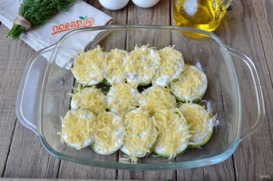 На каждый кружочек кабачка положите сметану с укропом, посыпьте тертым сыром. Разогрейте духовку.