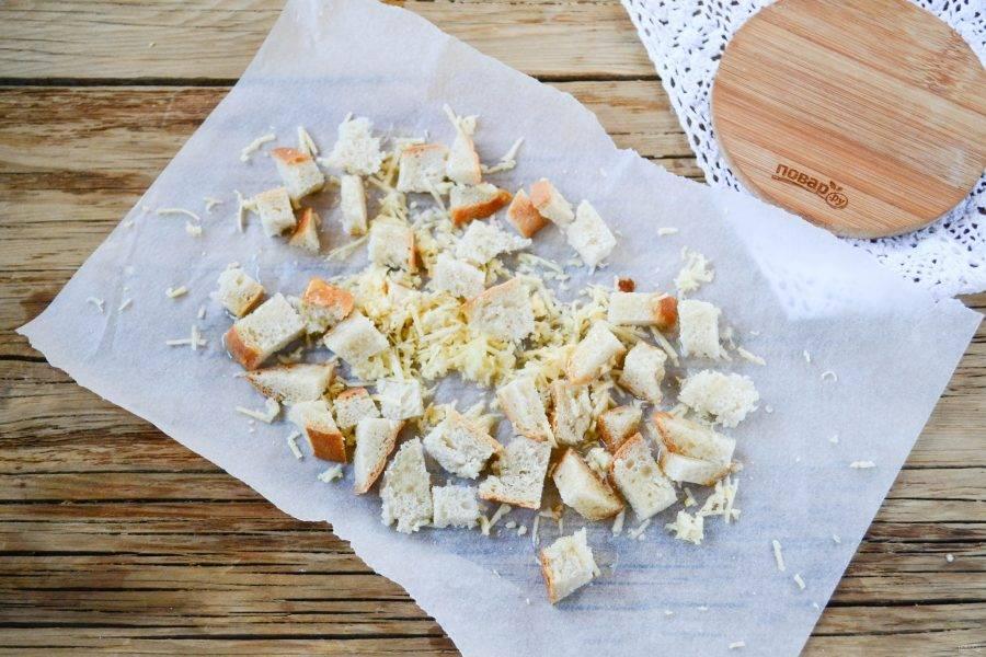 """Белый хлеб порежьте на небольшие кубики и выложите на пергамент. Выдавите пару зубчиков чеснока, натрите на мелкой терке сыр. Все это смешайте с хлебом, сверху сбрызните растительным маслом. Подсушите хлеб в микроволновке на функции """"Гриль"""" в течение 5 минут (или же это можно сделать в духовке)."""