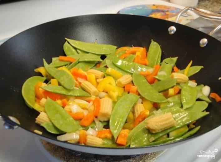 2.Ставим вок на огонь, наливаем подсолнечное масло и отправляем почищенный и порезанный лук, мягкую часть лимонной травы, мелко рубленный имбирь, рубленный сладкий перец, молодой горошек и кукурузу. Обжариваем овощи 2-4 минуты.