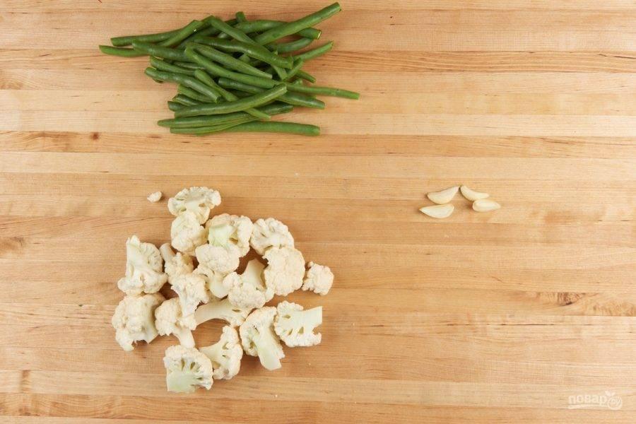 1. Подготовьте ингредиенты. Разделите на мелкие соцветия капусту. Фасоль разрежьте на половинки. Чеснок почистите от шелухи.