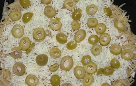 2. Сыр тоже трем на терке. Посыпаем картофельную массу сверху. Оливки измельчаем и тоже выложим в один слой.