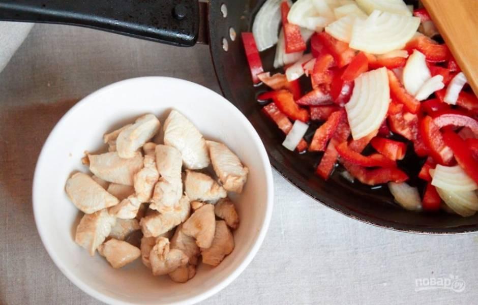 Шаг второй - в сковороде разогреваем немного растительного масла, обжариваем в нем кусочки курицы до готовности (около 7 минут на среднем огне). Курицу перекладываем в мисочку, в том же масле обжариваем перец и лук (еще минут 5, до прозрачности лука).