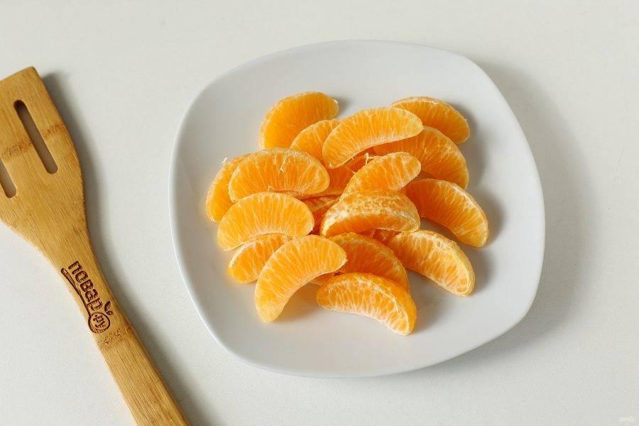 Мандарины очистите от кожуры и разделите на дольки. Один мандарин оставьте для верха.