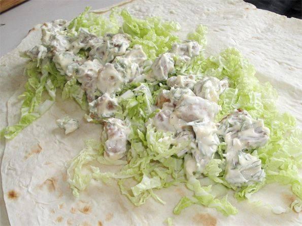 Разложите на столе лаваш, в середину выкладываем капусту, затем мясо с соусом.
