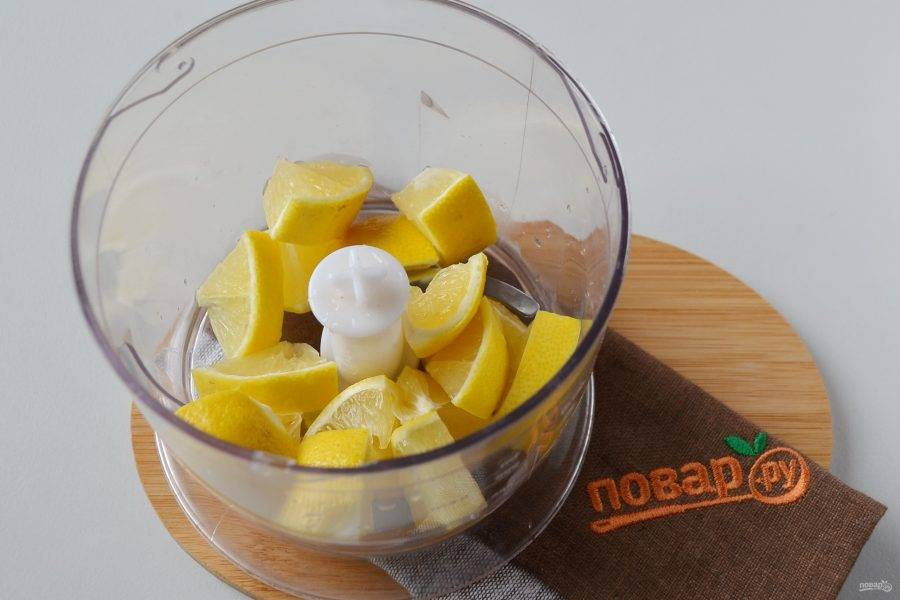 2. Лимон тщательно вымойте, ошпарьте кипятком, чтобы убрать горечь. Порежьте кусочками, удалите косточки. Положите лимон в чоппер и измельчите.