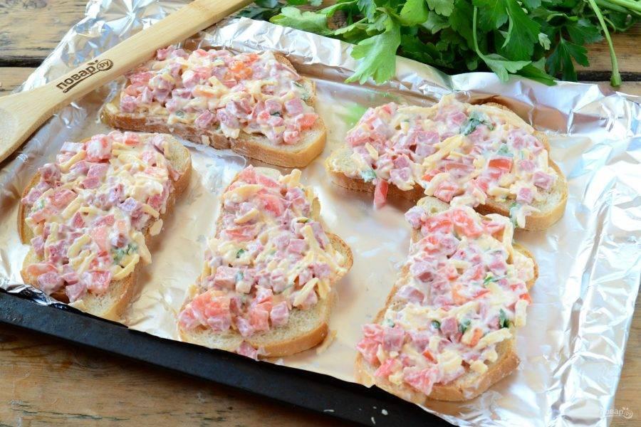 На противень выложите ломтики хлеба, сверху обильно выложите начинку, слегка придавите ложкой.