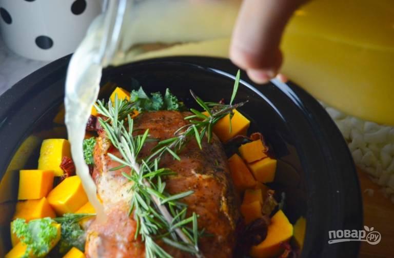 Тыкву порежьте некрупными кусочками, очистите чеснок, выложите это все, а также капусту, чечевицу, розмарин и порезаный лук в мультиварку или казанок. Влейте бульон, сверху положите мясо.