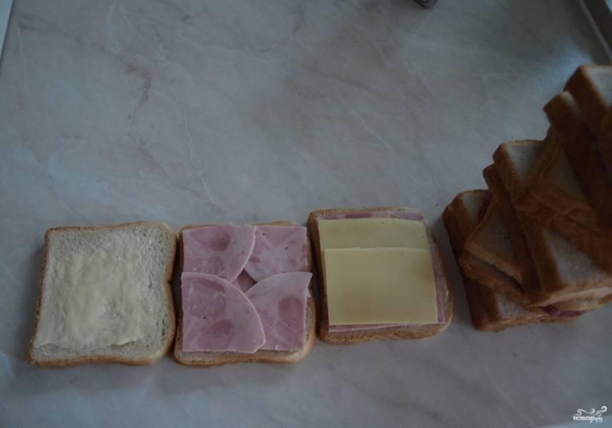 1. Смажем два кусочка маслом, наверх выкладыаем кусочки колбасы и сыра. Сверху накрываем вторым кусочком хлеба.