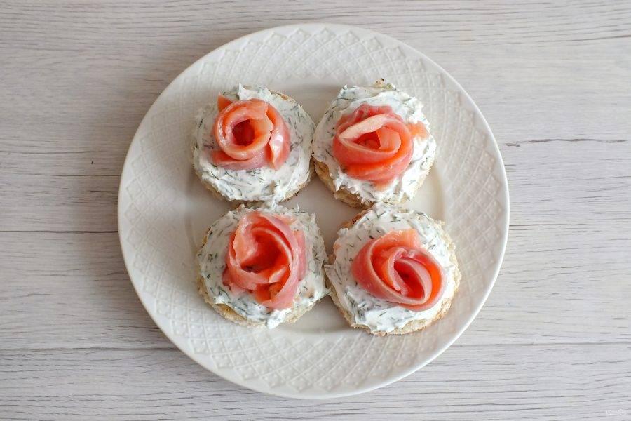 """Полоски из красной рыбы скрутите в трубочку, расправляя концы, придайте форму """"розочки"""". Переложите на хлеб с сыром."""