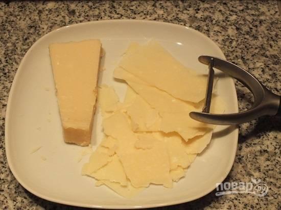 Сыр с помощью овощечистки настрогаем тонкими ломтиками.