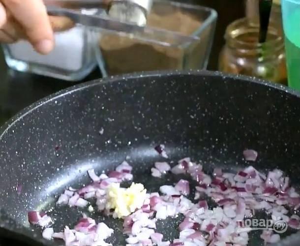 Нагрейте растительное масло на среднем огне в глубокой сковороде или казанке. Добавьте мелко нарезанный лук, измельченный чеснок и обжарьте их до золотистого цвета.
