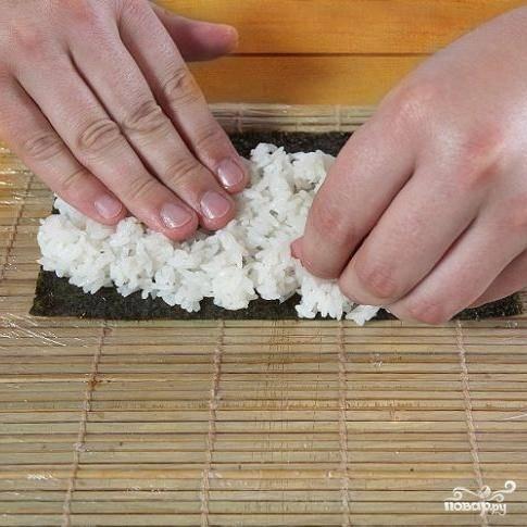 1. Выложить лист нори на циновку. Мокрыми руками взять рис и равномерно распределить по нори.