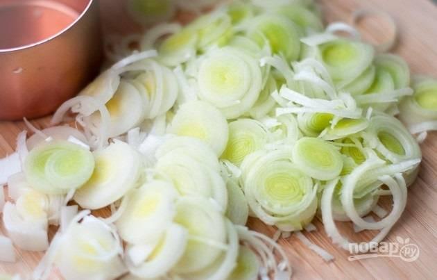 1. Вымойте и нарежьте тонко порей. В кастрюле растопите сливочное масло.