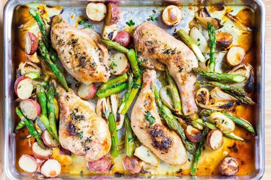 Добавьте на противень ароматные травы и отправьте все в духовку минут на 40, время от времени перемешивая овощи. Курицу смажьте маслом и посолите по вкусу, отправьте к овощам еще на 30 минут. Добавьте спаржу и готовьте еще 10 минут.