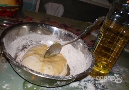 Потом в тесто влейте масло. Ещё раз хорошо замешайте. Оставьте тесто на 40 минут в тёплом месте под полотенцем.