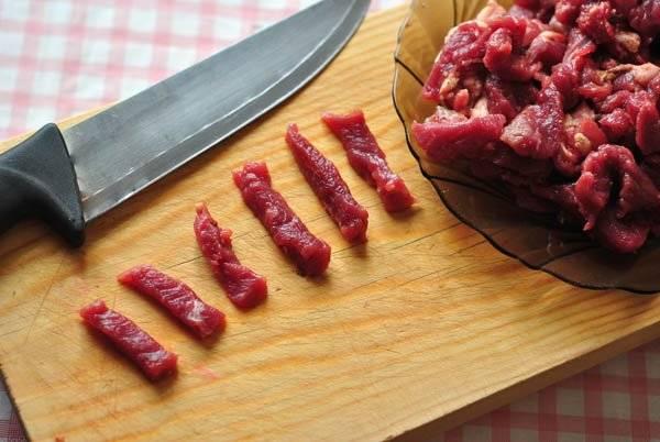Мясо режем на тонкие полоски и жарим на растительном масле на большом огне малыми порциями. Добавляем специи.