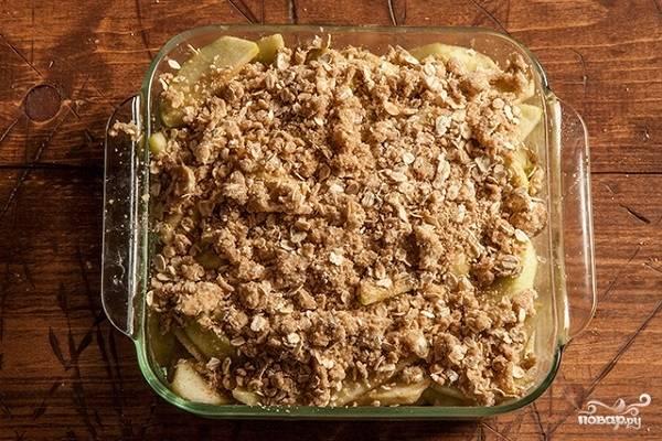 4. Присыпьте крошкой яблоки, отправьте форму в разогретую до 180 градусов духовку минут на 40-55 (в зависимости от размера формы). Подавайте к столу десерт теплым, при желании дополнив сливками или мороженым, например.