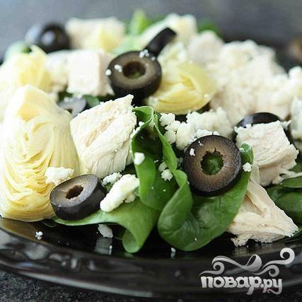 4. Разделить листья шпината поровну между четырьмя тарелками. Выложить поверх шпината равное количество куриных грудок, артишоков, маслин и сыра Фета.