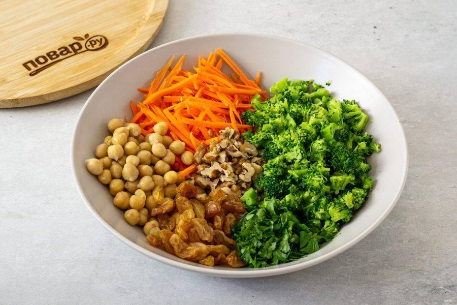 Мелко нарежьте брокколи. Морковь очистите и натрите на терке для моркови по-корейски. Петрушку и грецкие орехи мелко порубите. Консервированный нут промойте, откиньте на сито и дайте стечь жидкости. Изюм промойте, обсушите. Переложите все ингредиенты в глубокую миску.
